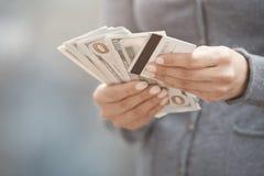 Женщина держа деньги и кредитную карточку наличных денег Стоковая Фотография RF