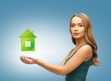 Женщина держа зеленый дом в ее руках Стоковые Фото