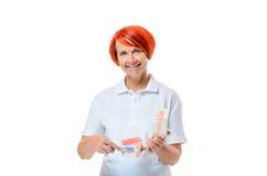Женщина держа зубную щетку над белой предпосылкой Стоковое фото RF