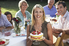 Женщина держа именниный пирог с семьей в саде Стоковое Фото