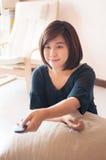 Женщина держа дистанционное управление с усмехаясь стороной стоковое изображение
