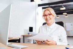 Женщина держа лист бумаги пока сидящ на офисе Стоковое Изображение RF