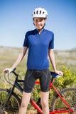 Женщина держа и стоя перед велосипедом стоковые фото
