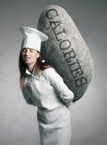 Женщина держа камень с принципиальной схемой калорий Стоковые Изображения