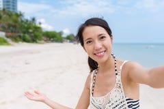 Женщина держа камеру для того чтобы принять selfie в пляже песка в солнечном дне стоковое изображение rf
