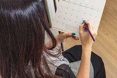 Женщина держа карандаш на календаре для назначать встречуа стоковое фото rf