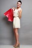 Женщина держа красные бумажные хозяйственные сумки Стоковая Фотография
