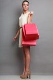 Женщина держа красные бумажные хозяйственные сумки Стоковая Фотография RF