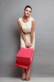 Женщина держа красные бумажные хозяйственные сумки Стоковое Изображение