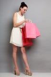 Женщина держа красные бумажные хозяйственные сумки Стоковые Изображения