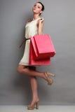 Женщина держа красные бумажные хозяйственные сумки Стоковое фото RF