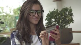 Женщина держа кредитную карточку и используя сотовый телефон для онлайн покупок сток-видео