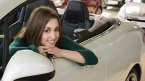 Женщина держа ключ автомобиля внутри автосалона Стоковое фото RF