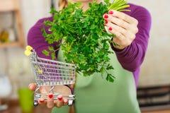 Женщина держа магазинную тележкау с петрушкой внутрь Стоковое Фото