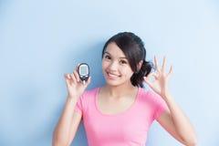 Женщина держа метр содержания глюкозы в крови стоковые фото