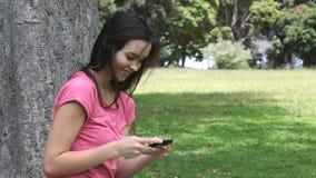 Женщина держа мобильный телефон в парке акции видеоматериалы
