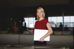 Женщина держа мобильный телефон и портативный компьютер с космосом экземпляра для вашего бренда пока стоящ в интерьере офиса, Стоковая Фотография