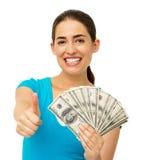 Женщина держа нас бумажные деньги пока показывающ жестами большие пальцы руки вверх Стоковые Изображения