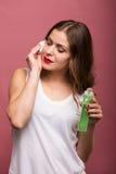 Женщина держа лосьон и пусковую площадку хлопка Стоковые Фото