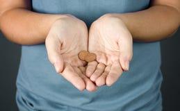 Женщина держа 2 пенни Стоковые Изображения
