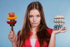 Женщина держа пилюльки и овощи здоровье внимательности рукояток изолировало запаздывания Стоковые Фотографии RF