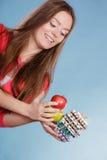 Женщина держа пилюльки и плодоовощи здоровье внимательности рукояток изолировало запаздывания Стоковое Изображение