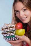 Женщина держа пилюльки и плодоовощи здоровье внимательности рукояток изолировало запаздывания Стоковые Фото