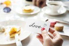 Женщина держа примечание влюбленности на малой карточке Стоковое Фото