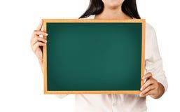Женщина держа пустую деревянную зеленую доску Стоковая Фотография RF