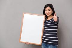 Женщина держа пустую доску и показывая большой палец руки вверх Стоковые Изображения