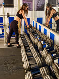 Женщина держа разминку гантели на спортзале Гантели в спортзале спорта Стоковое Фото