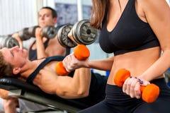Женщина держа разминку гантели на спортзале Стоковое Изображение