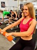 Женщина держа разминку гантели на спортзале Стоковое Фото