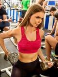 Женщина держа разминку гантели на спортзале Стоковые Фото