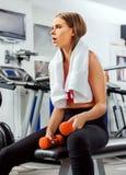 Женщина держа разминку гантели на спортзале Стоковая Фотография