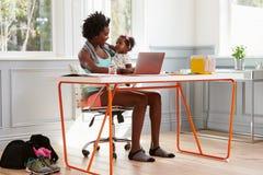 Женщина держа ребенка используя компьютер дома после работать Стоковые Фото