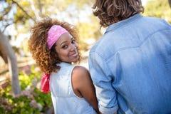 Женщина держа руки при человек идя в парк Стоковая Фотография RF