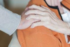 Женщина держа руку на плече старшей женщины Стоковые Фото