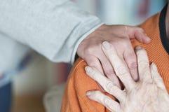 Женщина держа руку на плече старшей женщины стоковое изображение rf