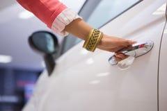 Женщина держа ручки автомобильной двери Стоковые Изображения