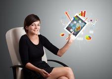 Женщина держа самомоднейшую таблетку с цветастыми диаграммами и диаграммами Стоковая Фотография RF