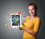 Женщина держа самомоднейшую таблетку с цветастыми диаграммами и диаграммами Стоковое фото RF