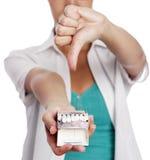Женщина держа сигареты и показывая большой палец руки вниз Стоковые Фотографии RF