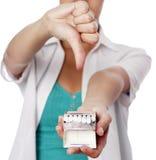 Женщина держа сигареты и показывая большой палец руки вниз Стоковое Изображение