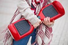 Женщина держа современное красное электрическое мини segway или завишет самокат доски Стоковые Фотографии RF