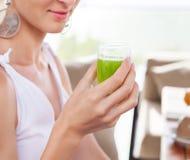 Женщина держа стекло зеленого сока в ее руке руки Стоковые Изображения