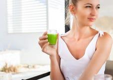 Женщина держа стекло зеленого сока в ее руке Стоковая Фотография RF