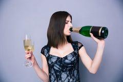 Женщина держа 2 стеклянное и выпивая шампанское от бутылки Стоковые Фотографии RF