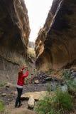 Женщина держа умный телефон и принимая фото на сценарную скалу внутри каньона в backlight Туристическая достопримечательность в в Стоковые Фотографии RF
