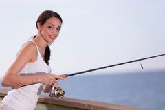 Женщина держа удя поляка и полагаясь на перилах стоковая фотография rf